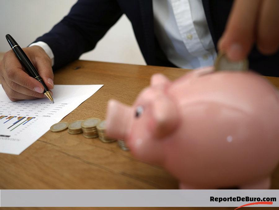 persona tomando notas y ahorrando dinero en alcancía